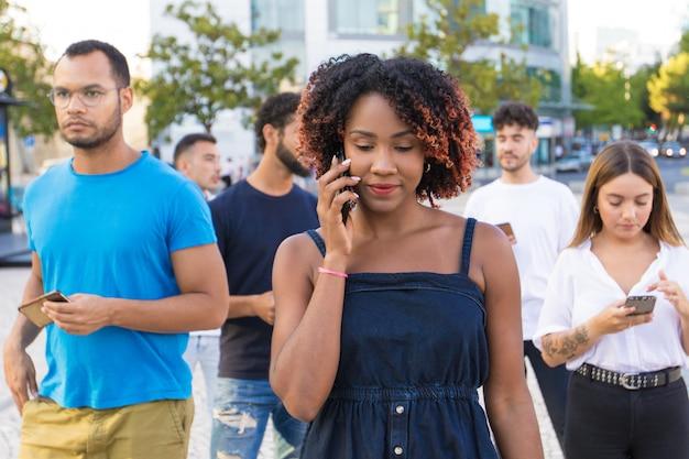 Grupo diverso de personas que usan sus teléfonos inteligentes mientras caminan Foto gratis