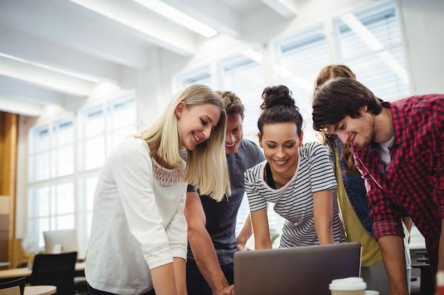 Grupo de ejecutivos de negocios usando la computadora portátil en su escritorio Foto gratis