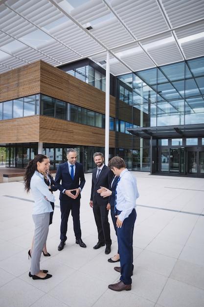 Grupo de empresarios interactuando fuera del edificio de oficinas Foto gratis