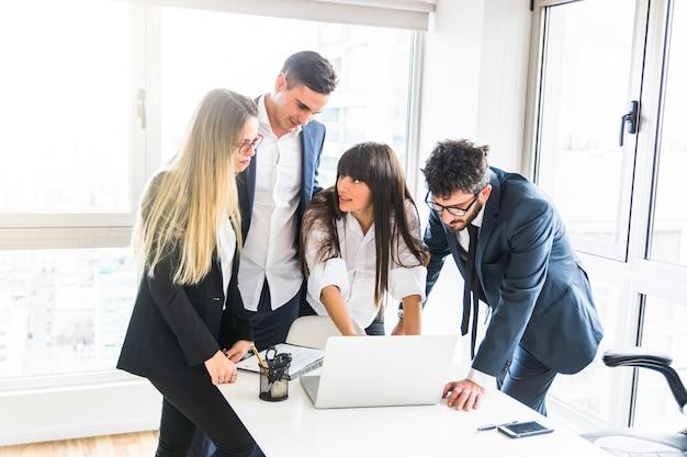 Grupo de empresarios de pie en la oficina mirando portátil en la oficina Foto gratis