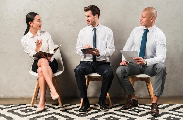 Grupo de empresarios sentados en una silla comunicándose unos con otros Foto gratis