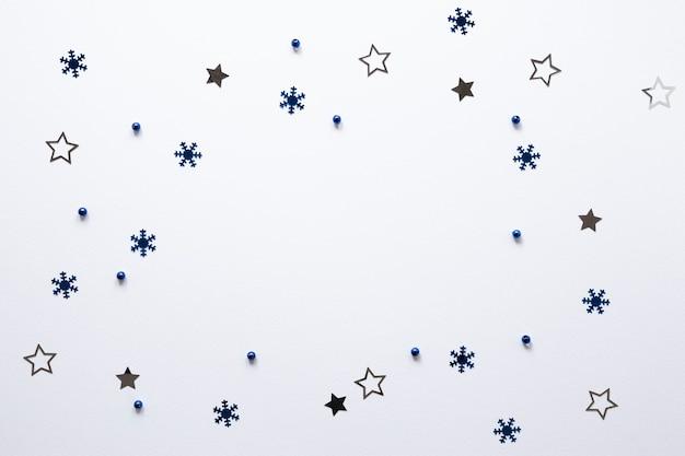Grupo de estrellas y copos de nieve sobre fondo blanco. Foto gratis