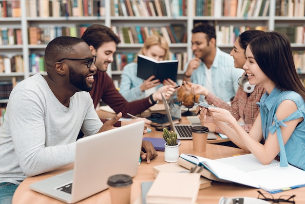 Grupo de estudiantes multiculturales étnicos sentado en la mesa. Foto Premium