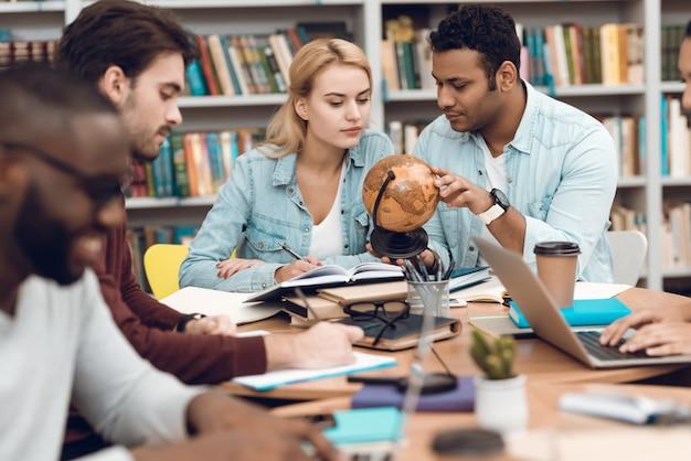 Grupo de estudiantes multiculturales étnicos sentados en la mesa. Foto Premium