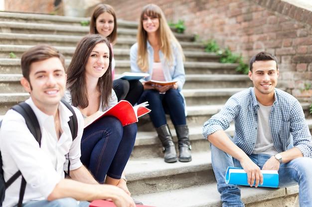 Grupo de estudiantes sonrientes sentados en una escalera Foto Premium