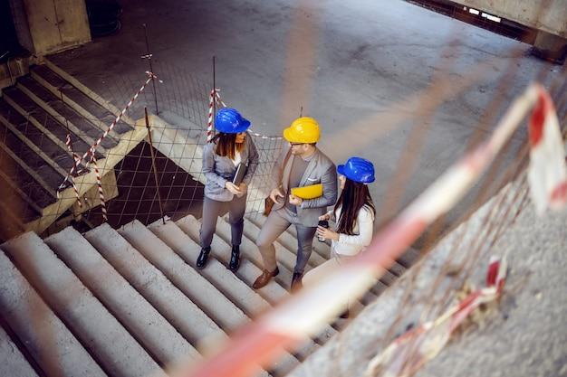 Grupo de exitosos arquitectos jóvenes e innovadores subiendo las escaleras y hablando de objetos. edificio en interior de proceso de construcción. Foto Premium