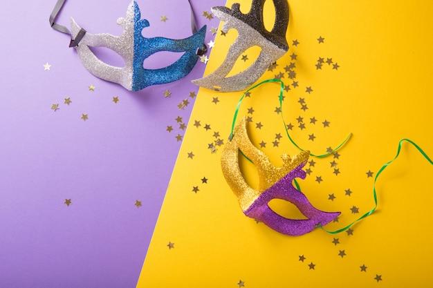 Un grupo festivo y colorido de carnaval o máscara de carnivale sobre un fondo amarillo púrpura. máscaras venecianas. Foto Premium