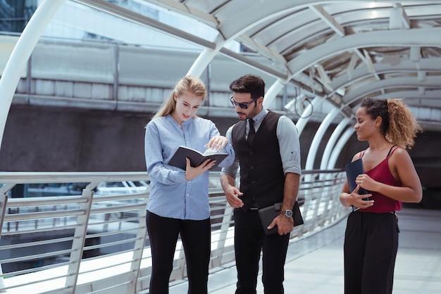 Grupo de gente de negocios que comprueba la fecha de la cita del cliente en el cuaderno mientras caminaba por la ciudad Foto Premium