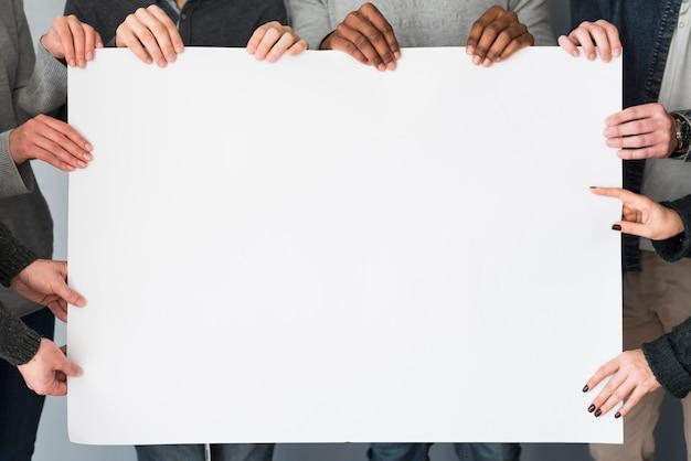 Grupo de gente sujetando plantilla de papel en blanco Foto gratis