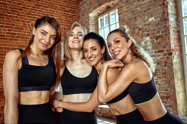 Un grupo de hermosas chicas deportistas después del entrenamiento se divierten, se cansan fácilmente, se felicitan mutuamente con excelentes resultados y un buen entrenamiento. sonriendo y posando para la cámara. Foto Premium