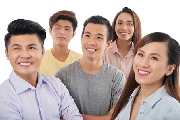 Grupo de hombres y mujeres asiáticos sonrientes de pie juntos y mirando hacia arriba Foto gratis