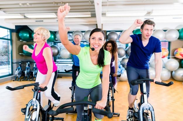 Grupo de hombres y mujeres girando en bicicletas de fitness en el gimnasio Foto Premium