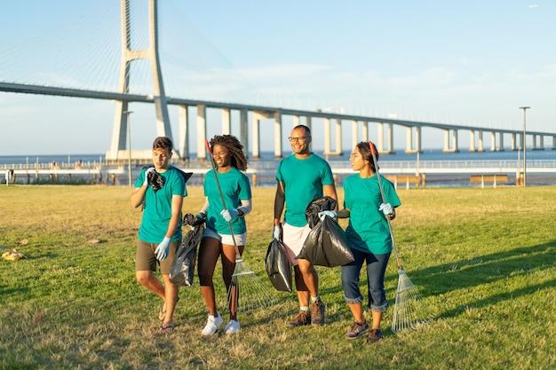 Grupo interracial de voluntarios llevando basura del césped de la ciudad Foto gratis