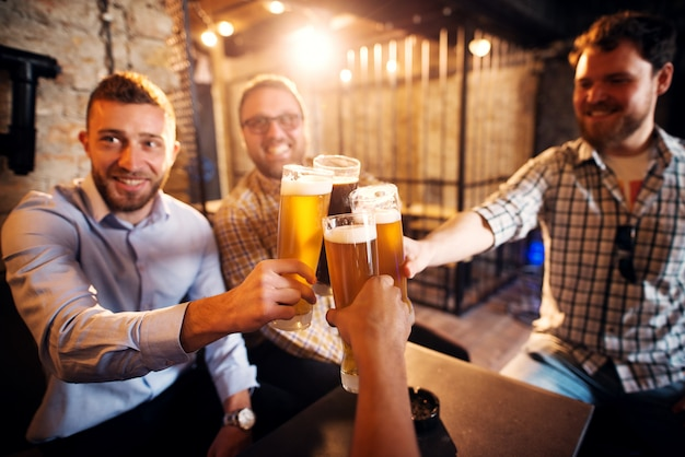 Grupo de jóvenes alegres tintineo de vasos con una cerveza en el pub soleado después del trabajo. Foto Premium