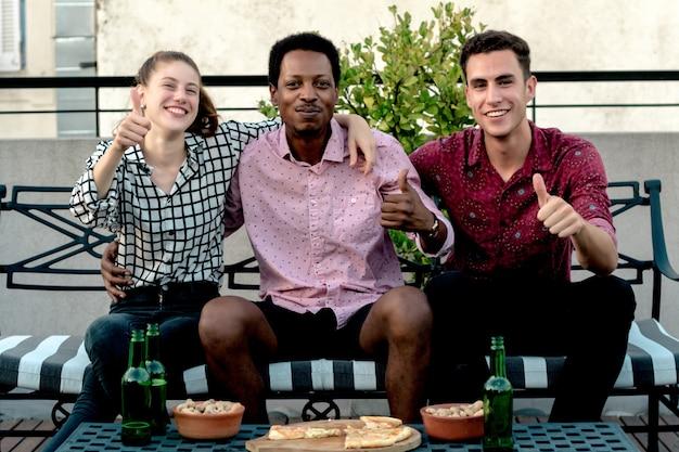 Grupo de jóvenes amigos con pizza y botellas de bebida. Foto Premium