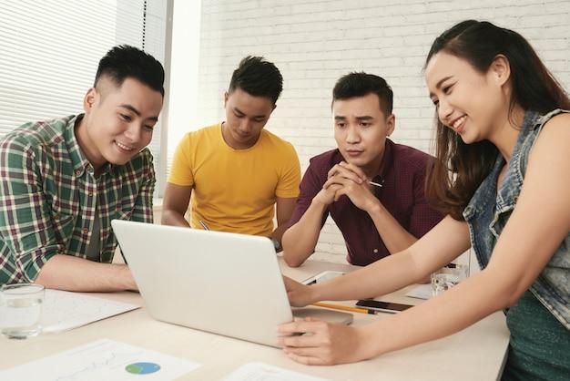 Grupo de jóvenes asiáticos casualmente vestidos de pie alrededor de la mesa y mirando la pantalla del portátil Foto gratis