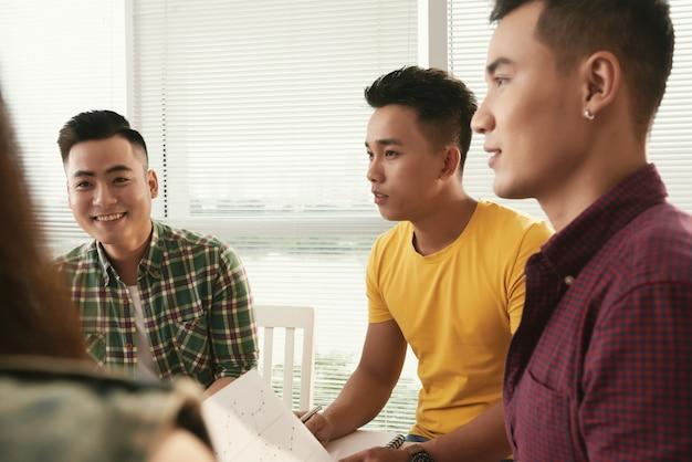 Grupo de jóvenes asiáticos vestidos casualmente hombres sentados y hablando en reunión Foto gratis