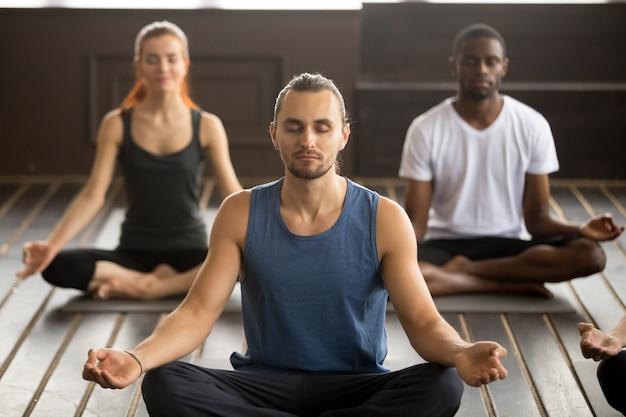Grupo de jóvenes deportistas sentados en el ejercicio de sukhasana Foto gratis
