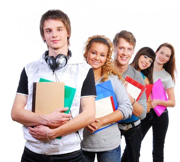 Grupo de jóvenes estudiantes alegres de pie con libros y bolsas Foto gratis