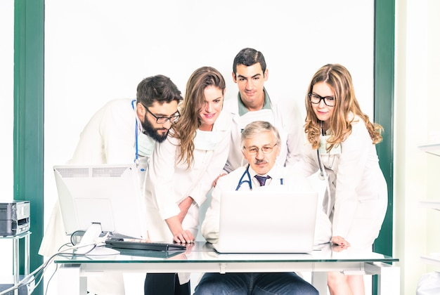 Grupo de jóvenes estudiantes de medicina con doctor senior en clínica de atención médica Foto Premium