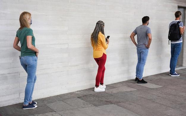 Grupo de jóvenes que esperan entrar en un mercado de tiendas mientras mantienen la distancia social en una línea durante el tiempo del coronavirus Foto Premium