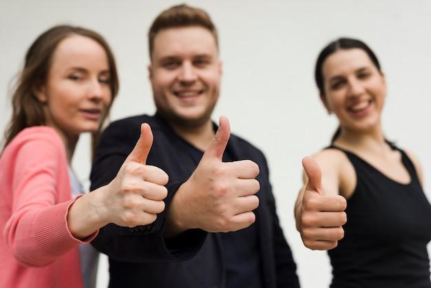 Grupo de jóvenes que muestran gesto de pulgar hacia arriba Foto gratis