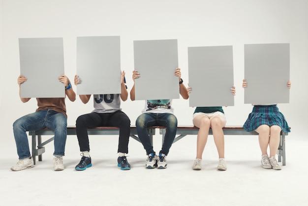 Grupo de jóvenes sentados sosteniendo, tiro de estudio de tablero de muestra en blanco Foto Premium