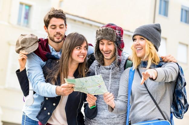 Grupo de jóvenes turistas turistas amigos animando con el mapa de la ciudad en el casco antiguo Foto Premium