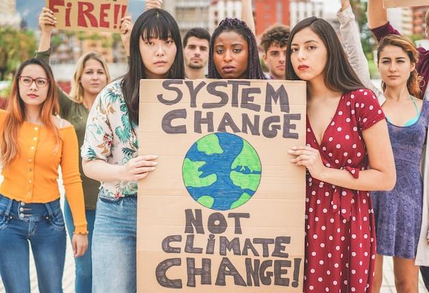 Grupo de manifestantes en carretera, jóvenes de diferentes culturas y razas luchan por el cambio climático. concepto de calentamiento global y medio ambiente Foto Premium
