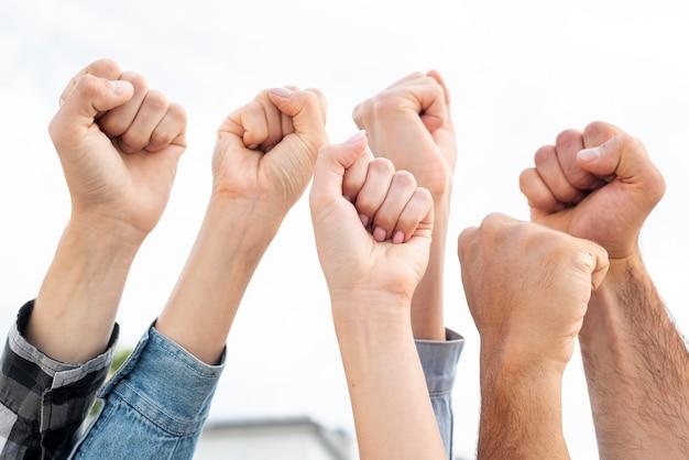Grupo de manifestantes levantando puños Foto Premium