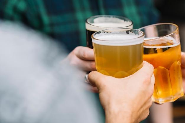 Grupo de la mano de un amigo animando con un vaso de cerveza Foto gratis