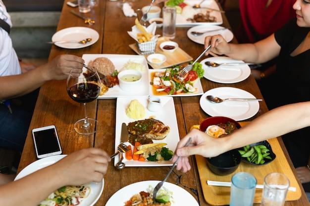 Grupo de manos de amigos con tenedor divirtiéndose comiendo comida de variedad en la mesa. Foto Premium