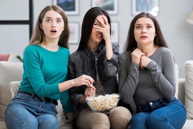 Grupo de mujeres adultas viendo una película de terror Foto gratis