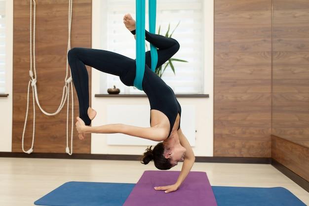 Un grupo de mujeres cuelga boca abajo en una hamaca. volar clase de yoga en el gimnasio. estilo de vida en forma y bienestar Foto Premium