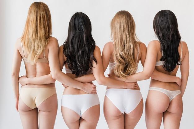 Grupo de mujeres delgadas en ropa interior de pie en abrazo Foto gratis