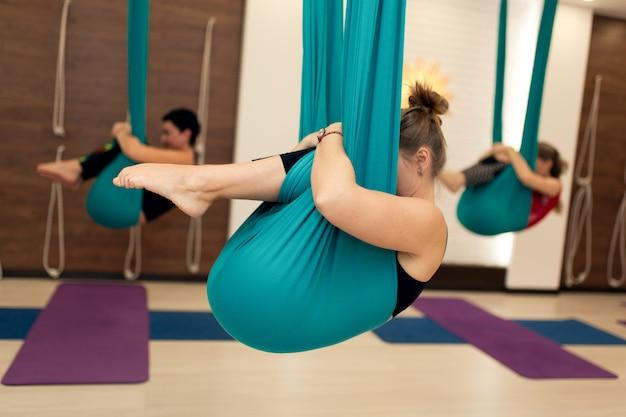 Un grupo de mujeres están colgadas en posición fetal en una hamaca. clase de yoga con mosca en el gimnasio Foto Premium
