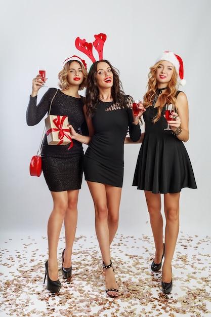 Grupo de mujeres de feliz celebración en lindos sombreros de disfraces de fiesta de año nuevo pasando un buen rato juntos. beber alcohol, bailar, divertirse sobre fondo blanco. longitud total. Foto gratis