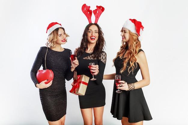 Grupo de mujeres de feliz celebración en lindos sombreros de disfraces de fiesta de año nuevo pasando un buen rato juntos. beber alcohol, bailar, divertirse sobre fondo blanco. Foto gratis