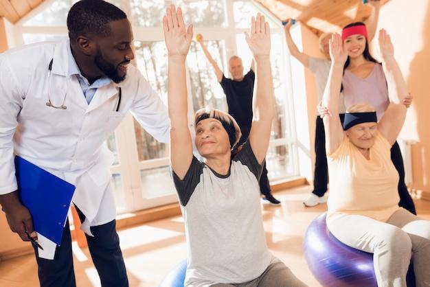 Grupo de mujeres y hombres de edad avanzada que realizan gimnasia terapéutica. Foto Premium