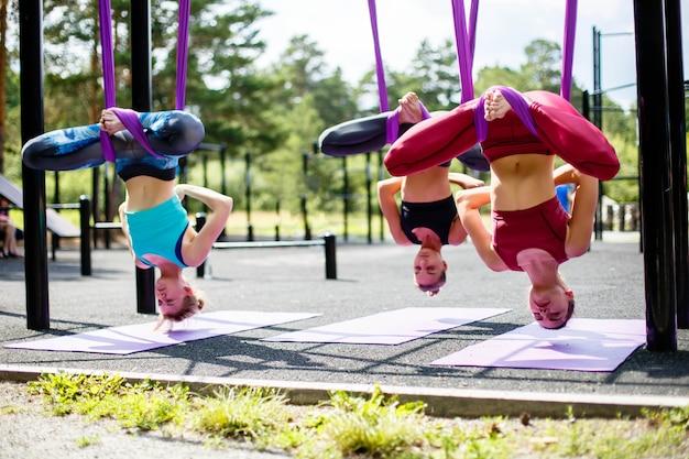 Un grupo de mujeres jóvenes que practican yoga aérea en una hamaca púrpura al aire libre Foto Premium