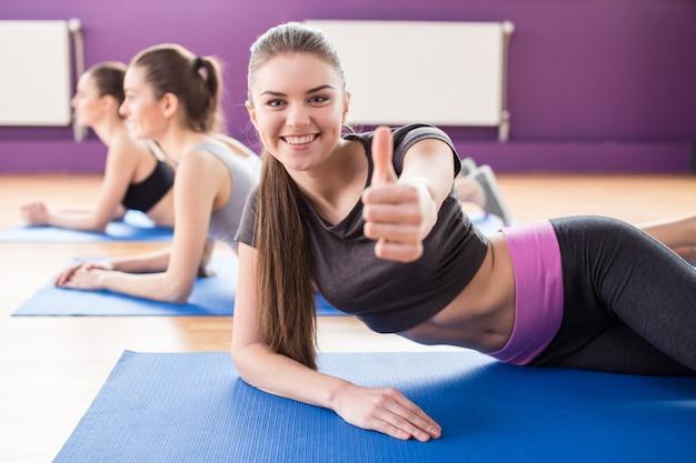 Grupo de mujeres sonrientes activas están entrenando en gimnasio. Foto Premium