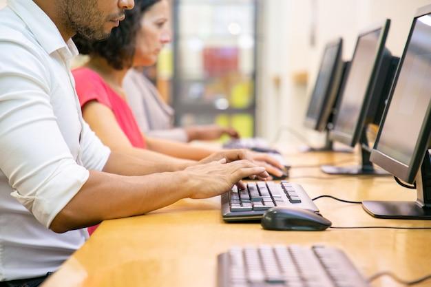 Grupo multiétnico de alumnos trabajando en clase de informática Foto gratis