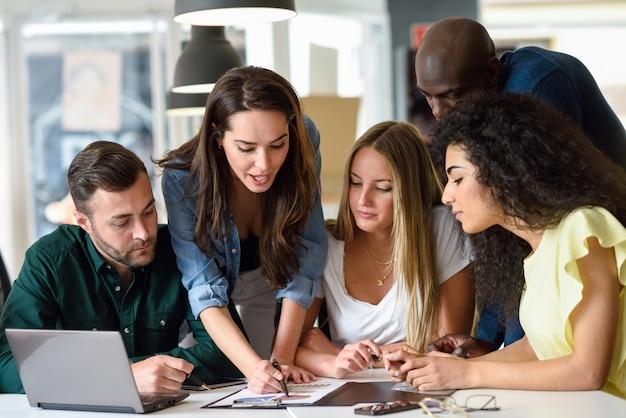 Grupo multiétnico de hombres jóvenes y de mujeres que estudian adentro. Foto gratis