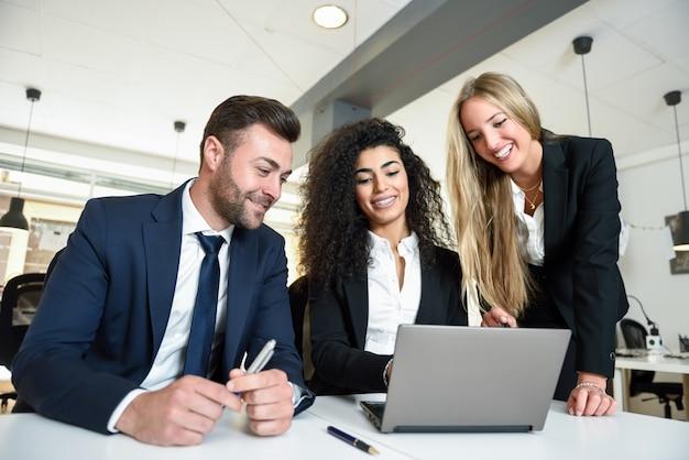 Grupo multiétnico de tres empresarios reunión en una oficina moderna. dos mujeres y un hombre llevando traje mirando un ordenador portátil. Foto gratis