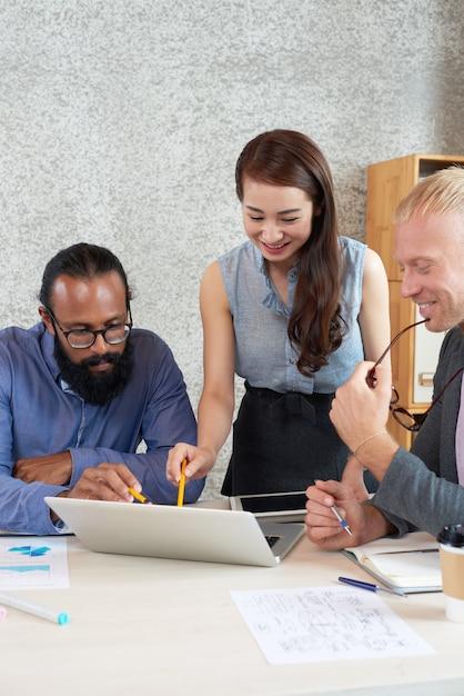 Grupo multinacional de colegas mirando la pantalla del portátil en la reunión de trabajo en la oficina Foto gratis