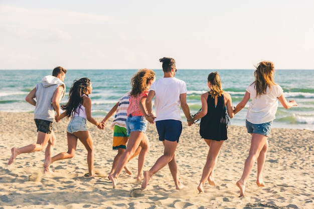 Grupo multirracial de amigos corriendo en la playa. Foto Premium