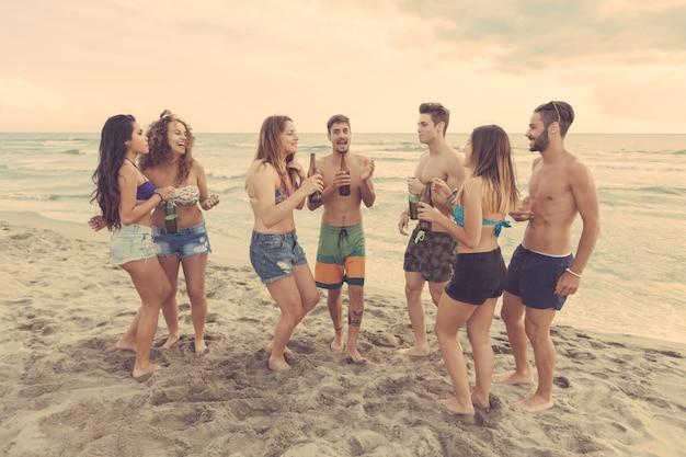 Grupo multirracial de amigos organizando una fiesta en la playa. Foto Premium