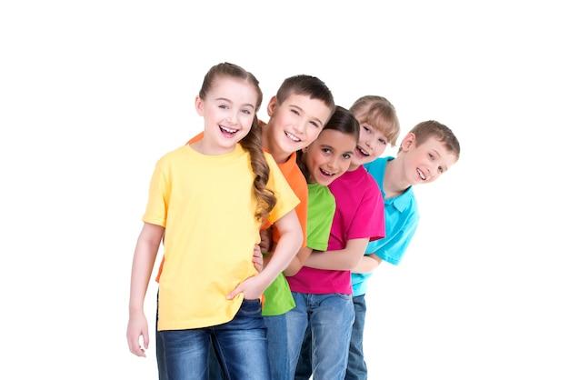 Grupo de niños felices en camisetas de colores están uno detrás del otro sobre fondo blanco. Foto gratis