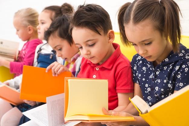 Grupo de niños leyendo libros Foto gratis