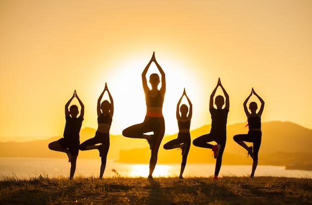 Grupo de niños participan en yoga con un entrenador en el océano. Foto Premium